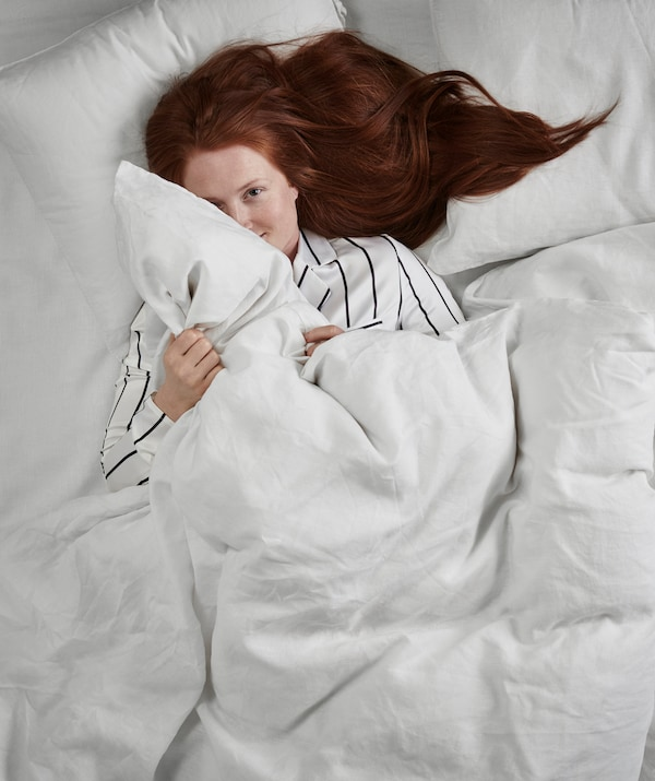A woman with long red hair and striped pajamas lies awake on her back in a double bed, clutching a duvet.