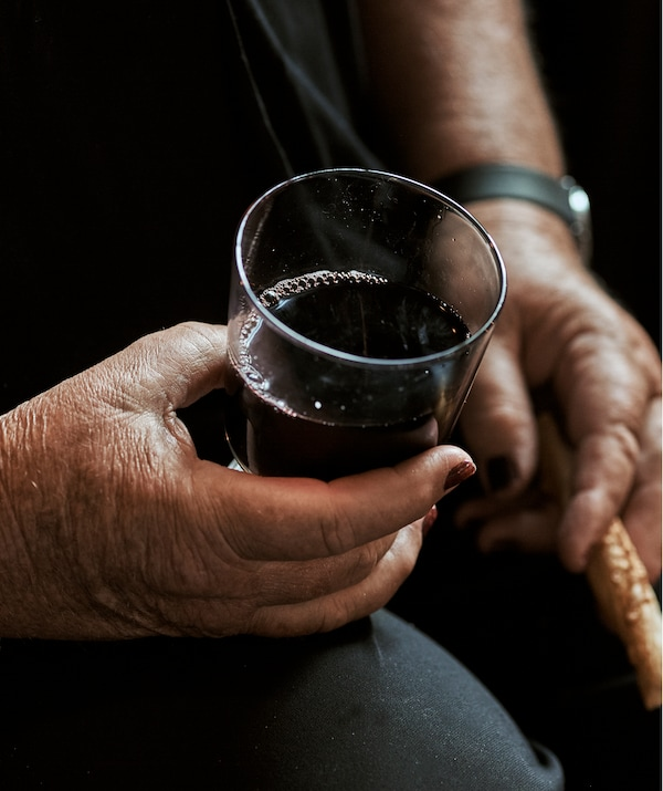 A woman with painted nails sits and holds a glass of wine in one hand and a breadstick in the other.