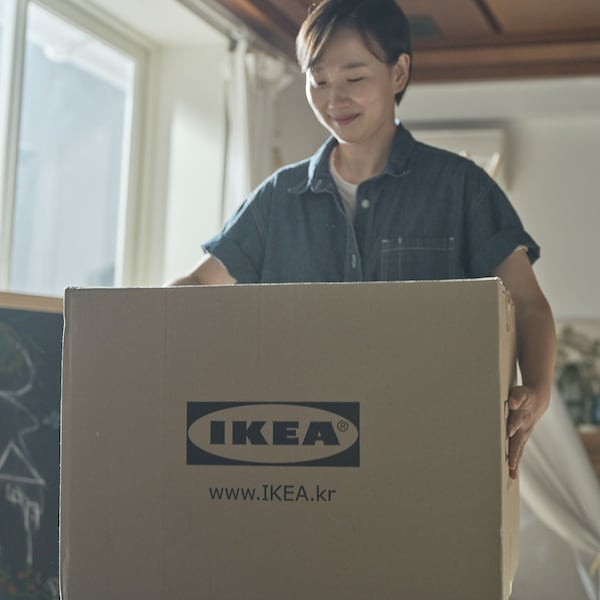 A woman with smile holding a box