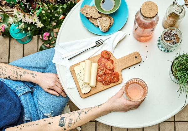 A woman with tattooed arms sits at a round, cream-colored table holding a glass, with a platter of cheese and tomatoes.