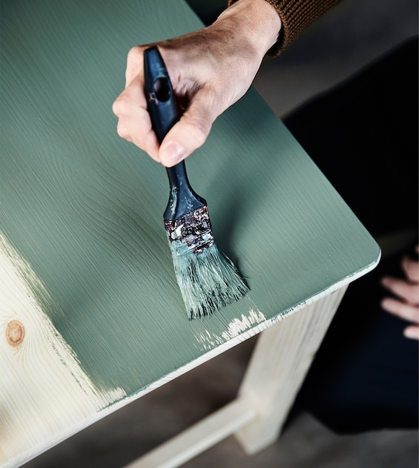 A woman's hand gives new life to an old chair by painting it in a new green colour.