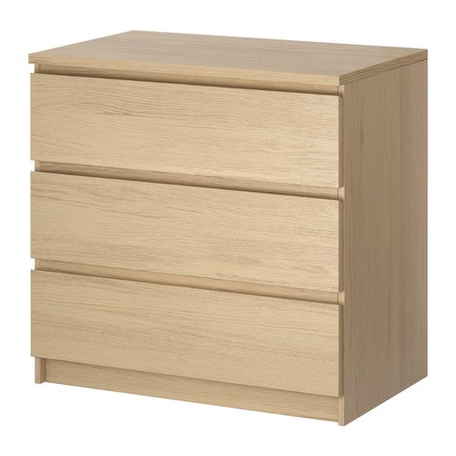 A wood colored 3 drawer chest against a white background.