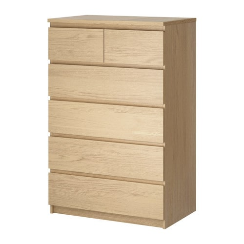 A wood colored 6 drawer chest against a white background.