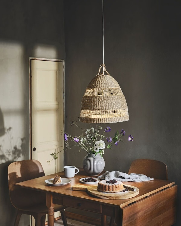 A wood dining table set for tea time with flowers and the TORARED lampshade hanging above.