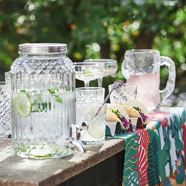 A wood picnic table with a glass drink dispenser, a glass pitcher and other summery glassware.