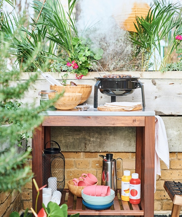 A wood trolley in an outdoor cooking area with a BBQ on its metal worktop and eatware and condiments on a shelf below.