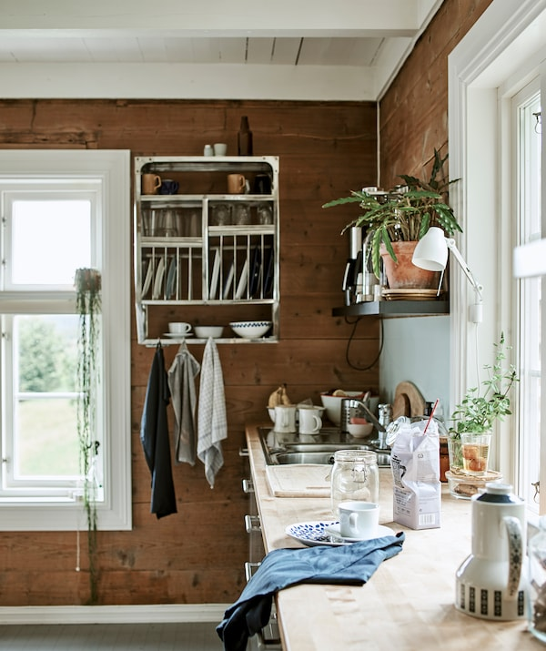 A wood worktop in a wood-panelled kitchen with open storage including a wall-mounted industrial cabinet with crockery.
