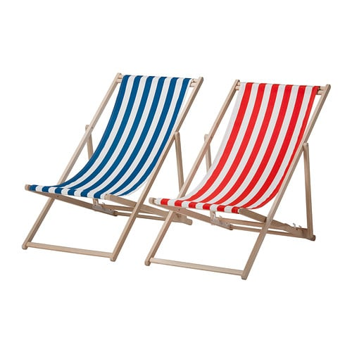 A wooden beach chair with a blue and white striped fabric seat next to one with a red and white striped seat.