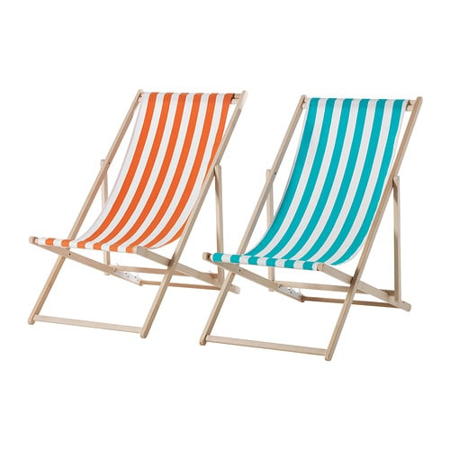A wooden beach chair with an orange and white striped fabric seat next to one with a blue and white striped seat.