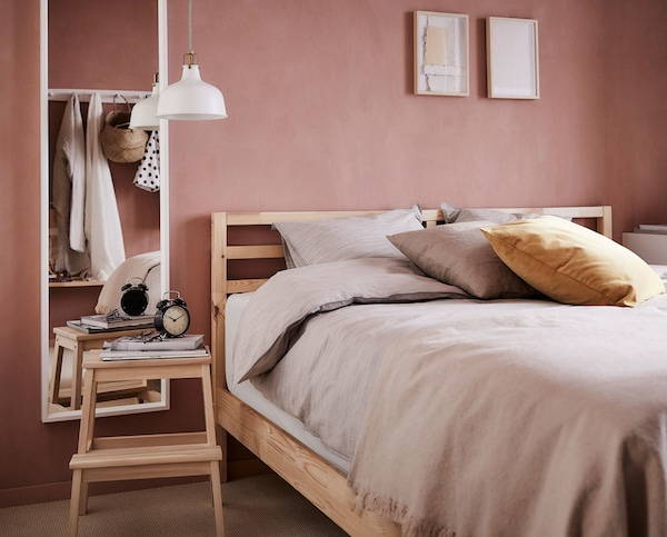 A wooden bed frame with beige bedding and a stool as a side table.