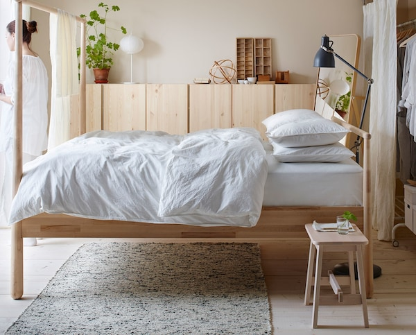 A wooden bed frame with white bedding.