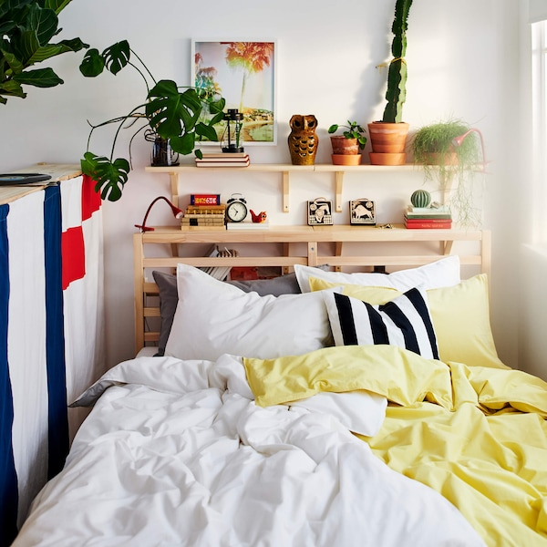 A wooden bed with white and yellow blankets, black and white pillows, and wooden shelves with plant pots.