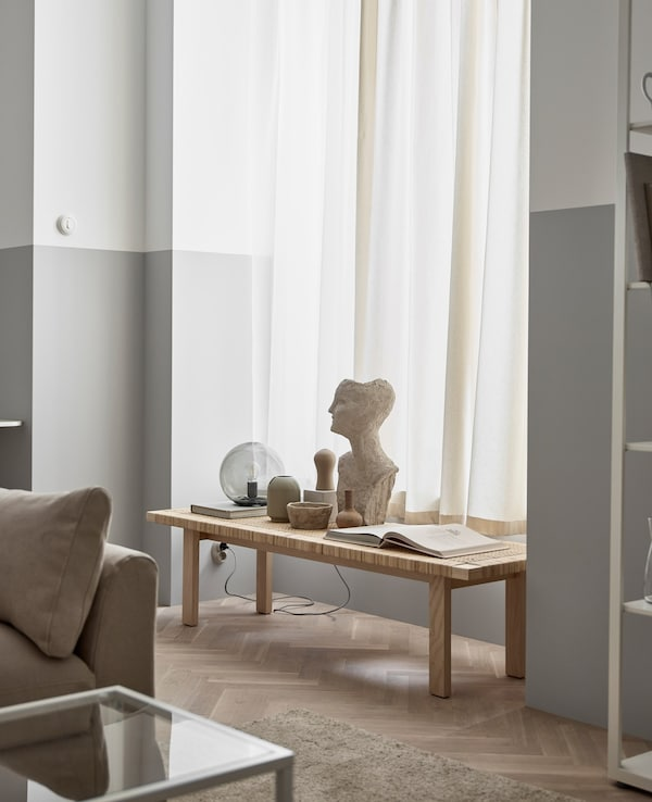 A wooden bench set into a window recess in this large living room displays decorating items, including a bust and book.