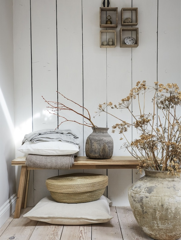 A wooden bench surrounded by rustic pots, dried foliage and natural textures.