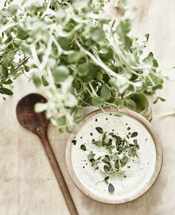 A wooden bowl of cashew cream garnished with thyme.
