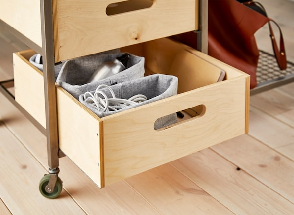 A wooden box being used for workspace storage in a movable bench.