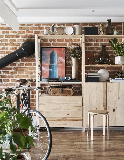 A wooden cabinet and shelves against a brick wall.