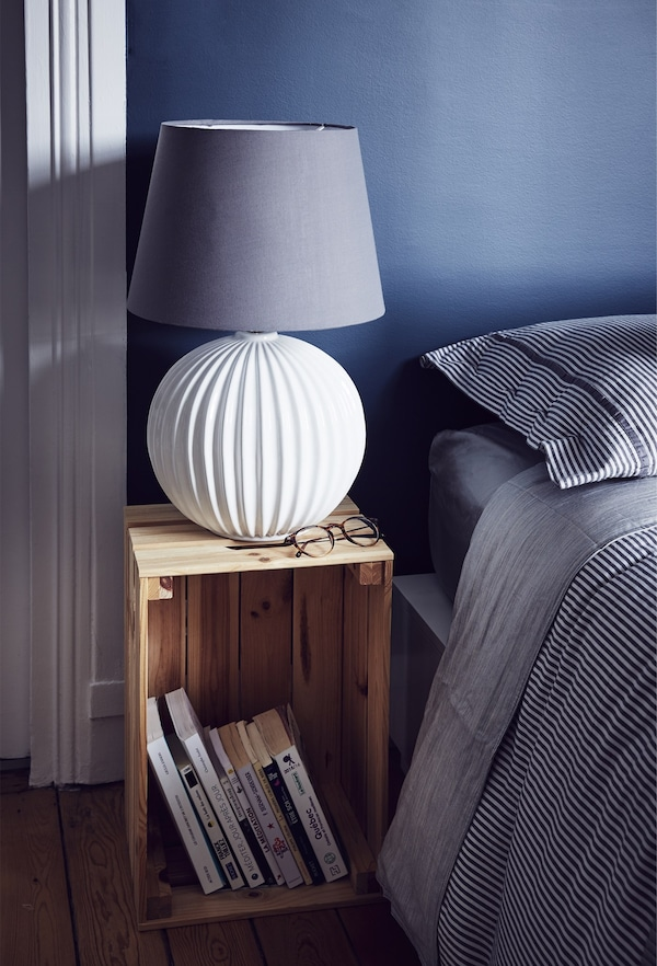 A wooden crate turned on its side to become a bedside table now holds a white lamp.