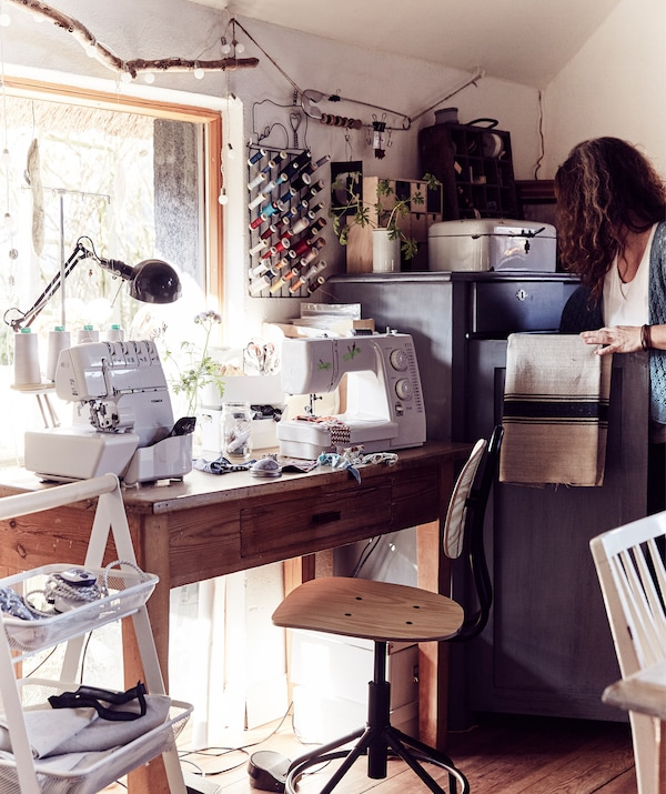 A wooden desk and swivel chair in front of a large window with sewing machines and craft supplies.