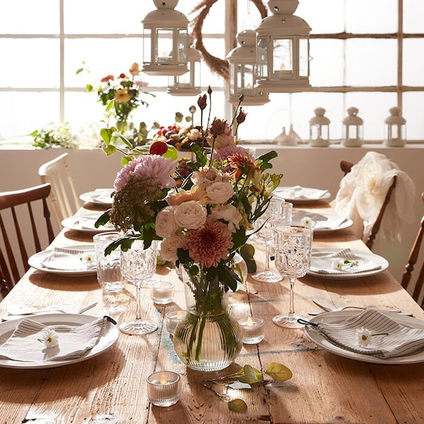 A wooden dinner table decorated with flowers and white crockery.