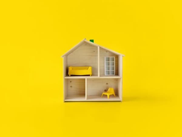 A wooden dollhouse with IKEA furniture inside.