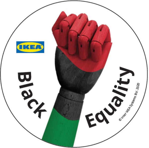 A wooden fist painted green, black and red with the words Black Equality and the IKEA logo within a circle.