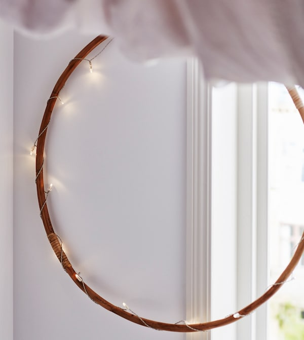 A wooden hoop is wound with a string of lights and hangs on the wall, partly infront of a window.