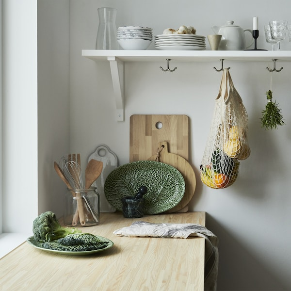 A wooden kitchen worktop with leaf-shaped plate, wooden chopping boards and tableware on a shelf.