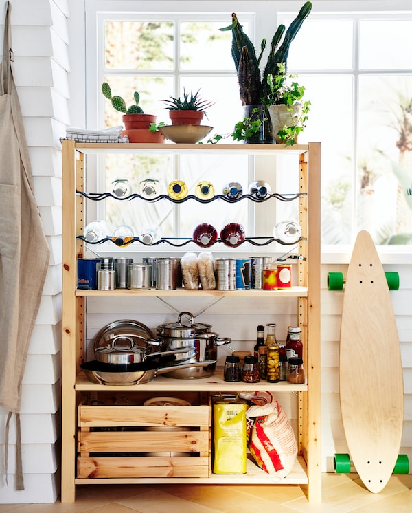 A wooden shelving unit with two bottle racks. Cookware, cans, jars, bottles and green plants are stored/standing here.