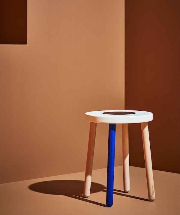A wooden stool with one blue leg and white top, in an orange room.