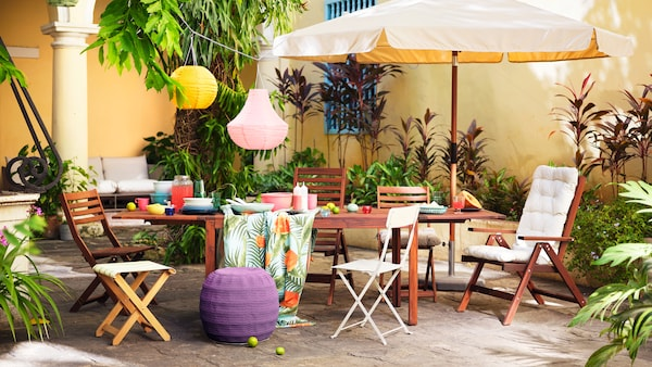 A wooden table and a variety of chairs set outside against a yellow wall, featuring an umbrella and colourful lanterns.