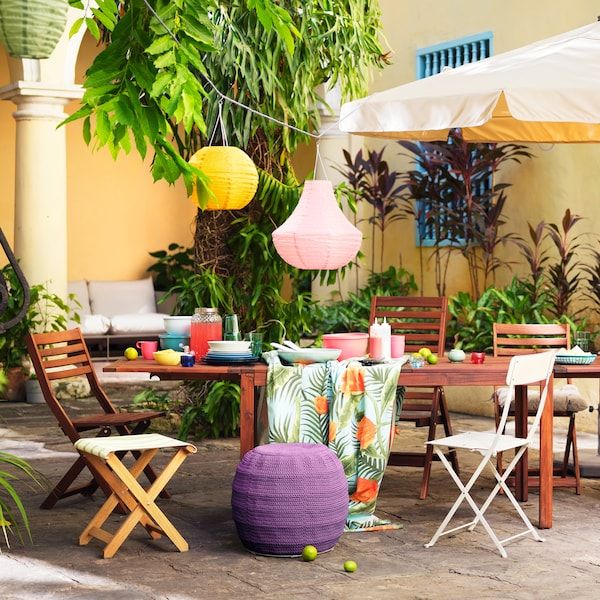 A wooden table set outside against a yellow wall, featuring colourful lanterns and a tablecloth with a tropical print.