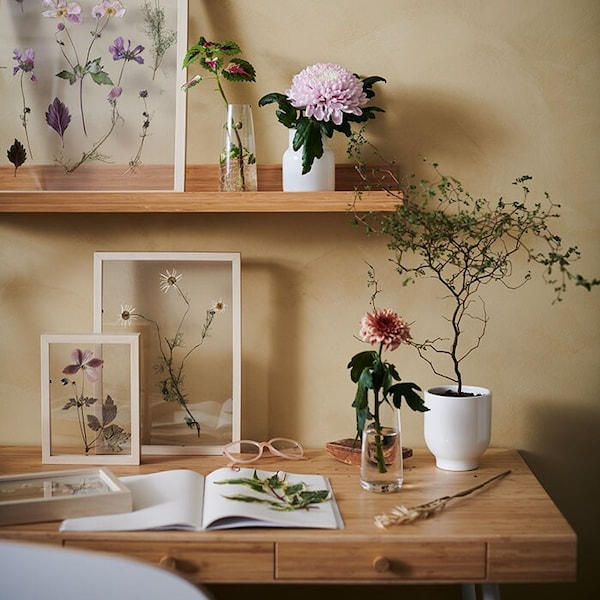 A wooden table with flowers in vases, and more flowers in pressed in frames.