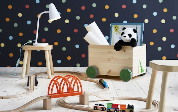 A wooden toy train set, a wooden toy crate with wheels and small wooden stools in a room with polka dot wallpaper.