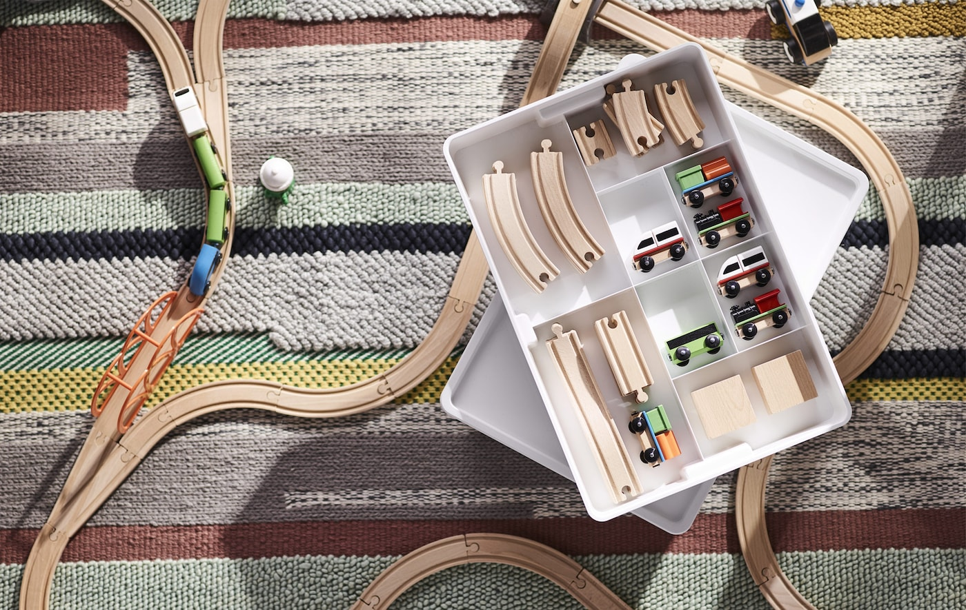 A wooden toy train set on a striped rug with a white storage box.