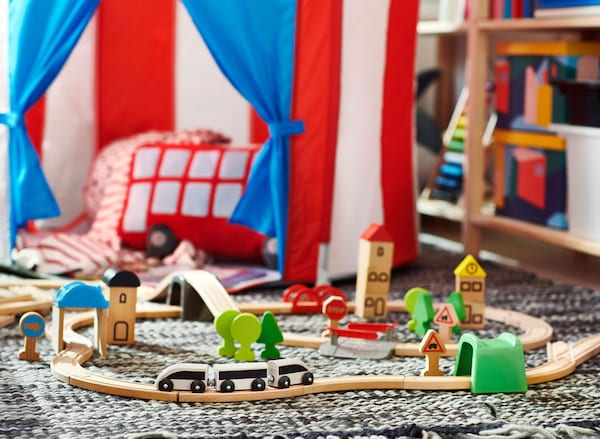 A wooden train set with cars and green scenery on a rug in front of a red and white striped circus tent.