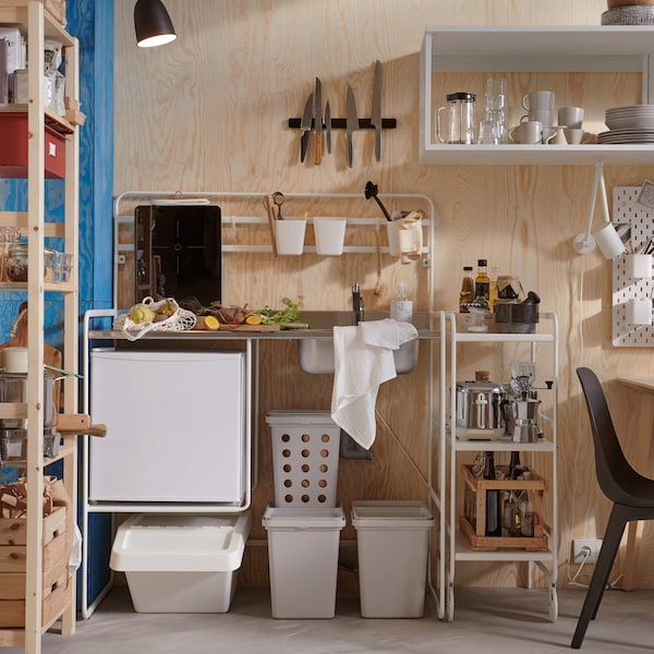 A wooden wall with several bins and shelving against the wall, with a modular mini kitchen.
