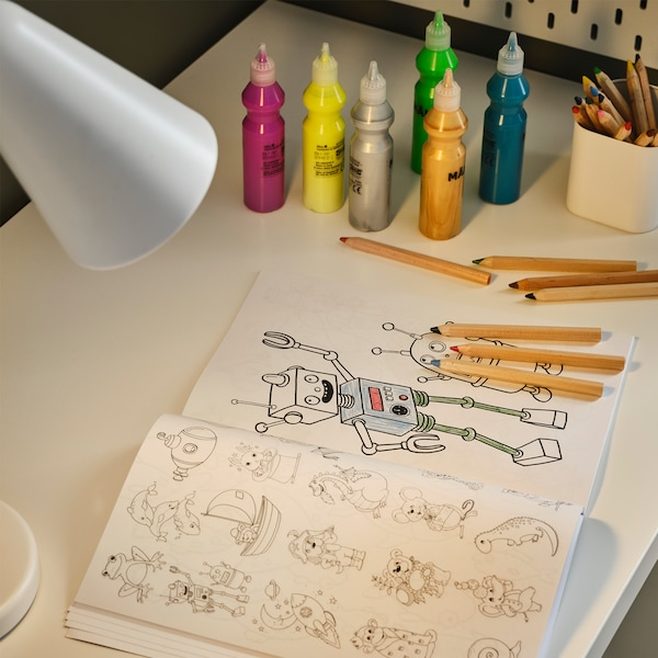 A work lamp illuminates a white desk, a colouring book, fluorescent/glitter paint in bottles and pens in different colours.