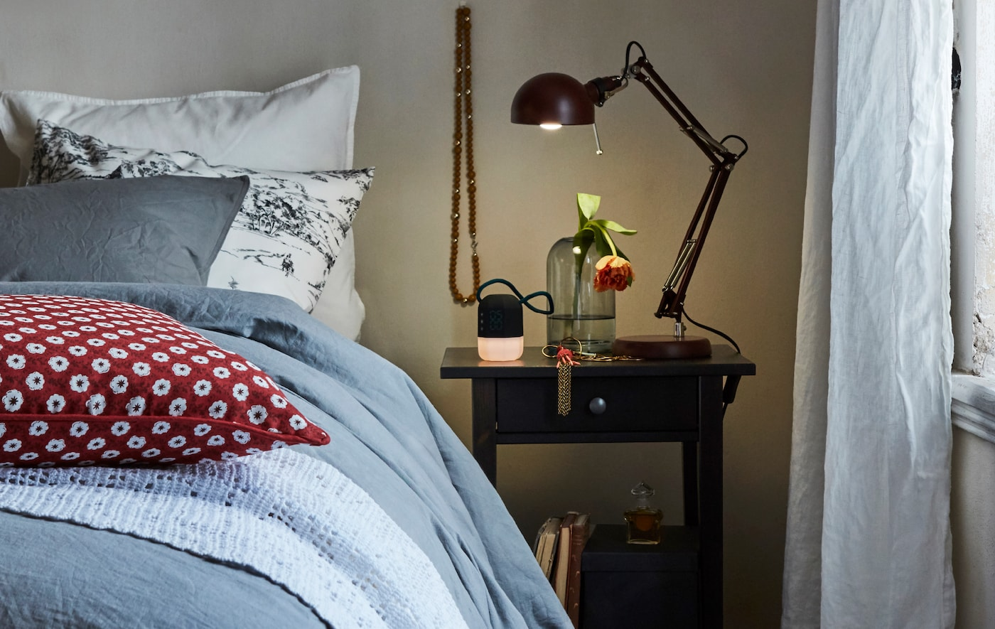 A work lamp on a table next to a bed shines light on a glass vase and alarm clock in a cosy bedroom.