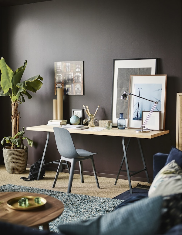 A work station made up of a chair and large desk set against the dark brown wall of a modern living room.