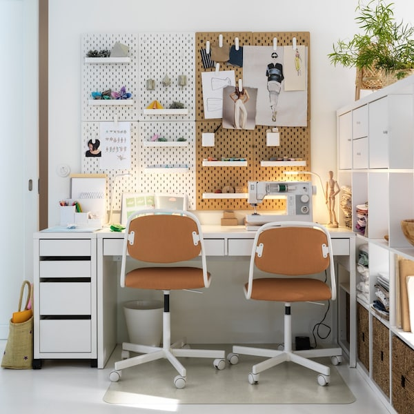 A work station with two chairs and peg board wall storage.
