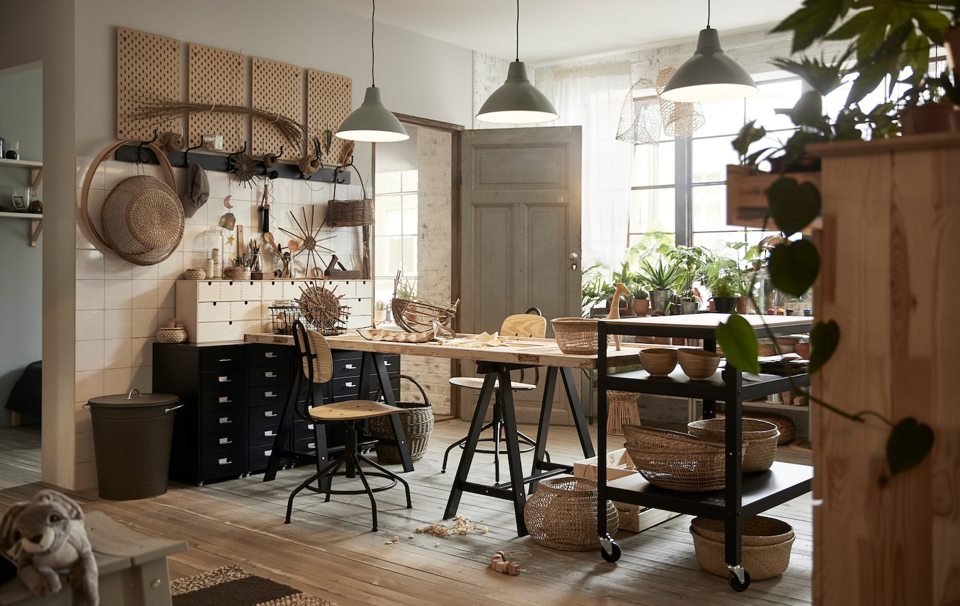 A workroom area filled with tables, swivel chairs, filing cabinets, hooks, baskets and plants.