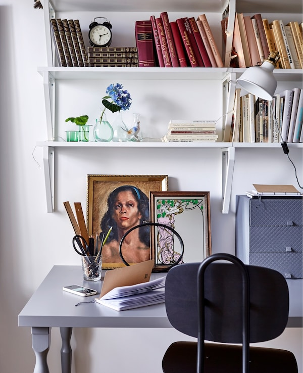A workspace in a white dorm room, including a black office chair, grey desk, artwork, and wall shelves with books.