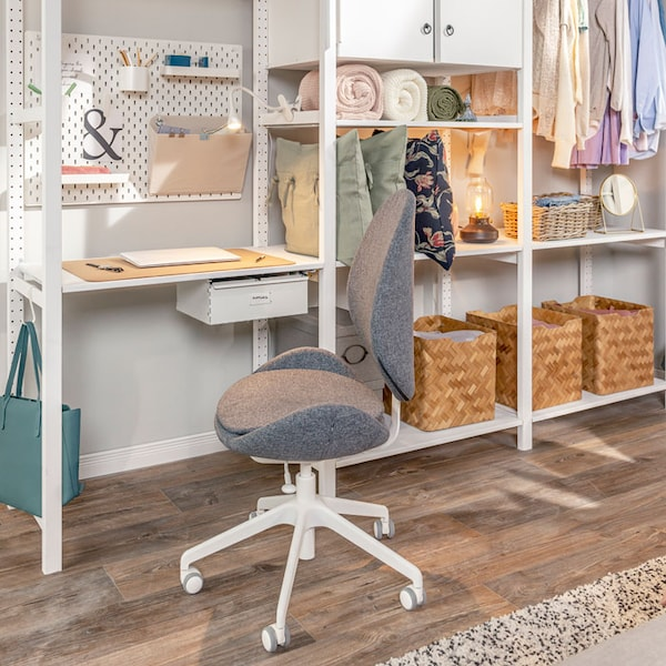 A workspace is set up in a bedroom using a storage system as a desk, a pegboard to store office supplies, and a swivel chair.