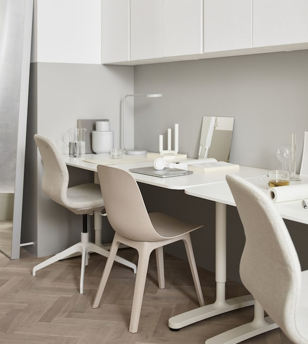A workspace made up of two desks against the wall of a cream-coloured living room with light wood floors.
