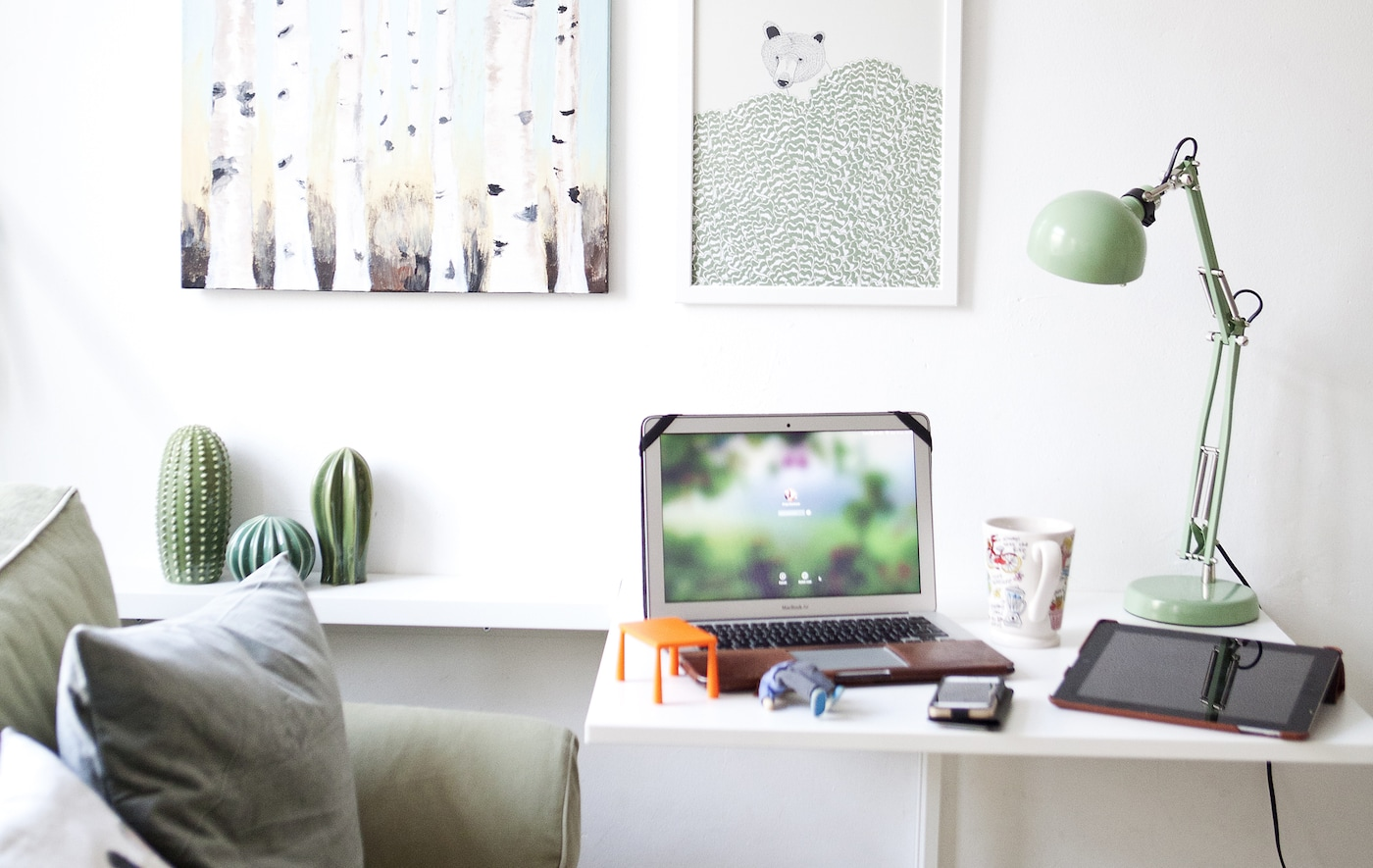 A workspace next to a sofa in a white living room.