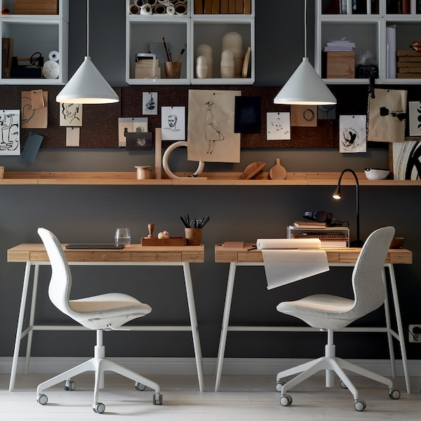 A workspace where two LÅNGFJÄLL office chairs sit at LILLÅSEN desks, with shelving, memo boards and white pendant lamps.