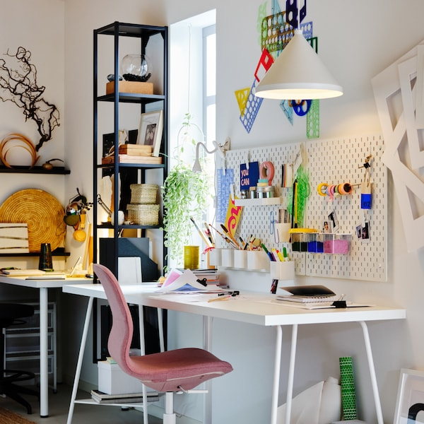 A workspace with a white LAGKAPTEN/TILLSLAG table, a LÅNGFJÄLL office chair, plus white pegboards and a pendant lamp.