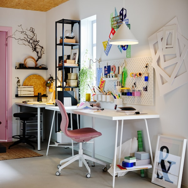 A workspace with a white LAGKAPTEN/TILLSLAG table, light brown-pink LÅNGFJÄLL office chair, plus white pegboards and pendant.