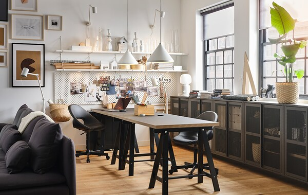 A workspace with two black tables and two black swivel chairs, two white pendant lamps and white wall shelves.